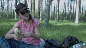 Two beautiful young women discuss the composition of the product. In nature, during lunch, the girls are following. Calories. Women with glasses in the park stock footage