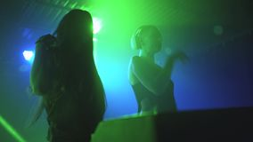 Two beautiful young women DJ play the music on the mixing console in the nightclub. In Odessa stock video
