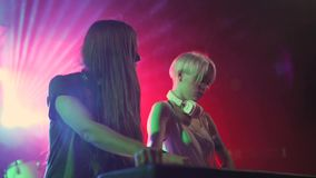 Two beautiful young women DJ play the music on the mixing console in the nightclub. In Odessa stock footage