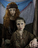 Two beautiful young women dressed as gypsies. One women has long, red, curly hair and one women has brown hair pulled back with silver and rhinestone head Royalty Free Stock Image