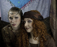 Two beautiful young women dressed as gypsies. One women has long, red, curly hair and one women has brown hair pulled back with silver and rhinestone head Royalty Free Stock Images