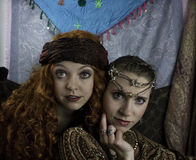 Two beautiful young women dressed as gypsies. One women has long, red, curly hair and one women has brown hair pulled back with silver and rhinestone head Royalty Free Stock Photos