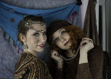 Two beautiful young women dressed as gypsies. One women has long, red, curly hair and one women has brown hair pulled back with silver and rhinestone head Stock Images