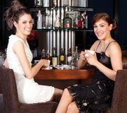 Two beautiful young women drinking coffee at bar Royalty Free Stock Images
