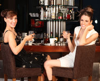 Two beautiful young women drinking water at bar Royalty Free Stock Photos