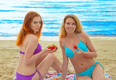 Two beautiful young women  eating a strawberry. Royalty Free Stock Photography