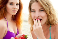 Two beautiful young women  eating a strawberry. Royalty Free Stock Image