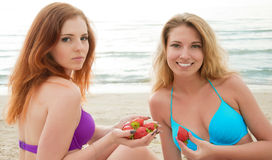 Two beautiful young women  eating a strawberry. Stock Images