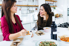 Two beautiful young women eating vegetables soup in the kitchen. Royalty Free Stock Images