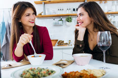 Two beautiful young women eating vegetables soup in the kitchen. Royalty Free Stock Photo