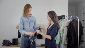 Two beautiful young women are engaged in the analysis of the wardrobe. Girlfriends choose outfits and pick up images. Modern women try to look stylish stock video
