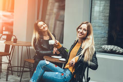 Two beautiful young women in fashion clothes having rest talking and drinking coffee in restaurant outdoor. Concept of friendship lifestyle fashion. sunny day royalty free stock photo