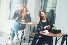 Two beautiful young women in fashionable wears sitting outdoor in cafe and using smartphones while drinking coffee. Business messa stock image