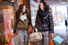 Two women out shopping. Two beautiful young women friends out shopping together in a mall with their hands full of colourful carrier bags Stock Photos