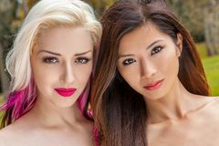 Two beautiful young women or girls one blonde and one Chinese Asian royalty free stock images