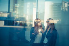 Two beautiful young women through glass Royalty Free Stock Photos
