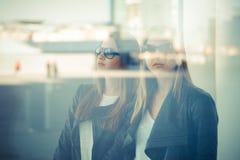 Two beautiful young women through glass Stock Photo