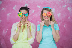 Two beautiful young women hides eyes with sweet lollipops. Two beautiful young women hides eyes with sweet lollipops over pink background. Holiday concept Stock Images