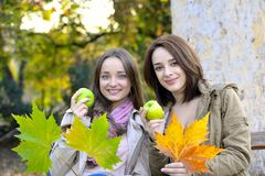 Two beautiful young women holding green apples and smiling Stock Photo