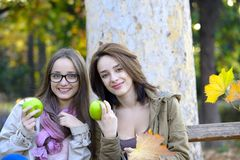 Two beautiful young women holding green apples and smiling Royalty Free Stock Image