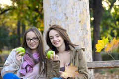 Two beautiful young women holding green apples and smiling Stock Image