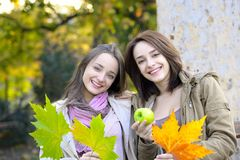 Two beautiful young women holding green apples and smiling Royalty Free Stock Photo