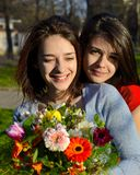 Two beautiful young women hugging and holding bouquet Stock Image