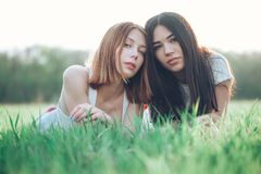 Two young women lie on the iawn. Two beautiful young women lie on the grass outdoors. Best friends Stock Image