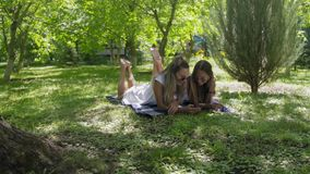 Two beautiful young women lie on green grass in park. HD stock video footage
