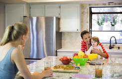 Two beautiful young women and little baby girl in the kitchen Royalty Free Stock Image