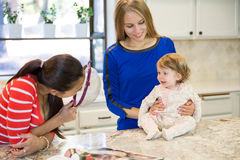 Two beautiful young women and little baby girl in the kitchen Stock Photography