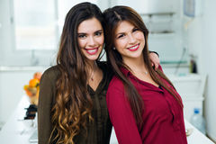 Two beautiful young women looking at camera in the kitchen. Stock Photos