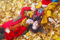 Two beautiful young women lying on yellow leaves Royalty Free Stock Images