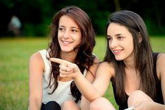 Two beautiful young women in a park pointing Royalty Free Stock Images