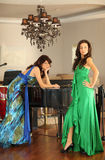 Two beautiful young women at a piano Royalty Free Stock Photography