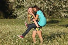 Two Beautiful Young Women Piggy- Backing In Meadow Stock Photography
