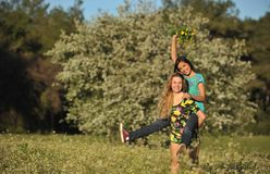 Two beautiful young women piggy-backing in meadow Royalty Free Stock Images