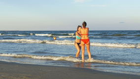 Two beautiful young women playing at the beach and dancing. Two beautiful young women playing on the beach and dancing stock video footage