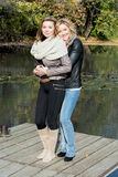 Two beautiful young women and pond in the autumn park Stock Images