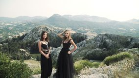 Two beautiful young women in posh black dresses posing together on camera against the background of a mountain landscape stock video