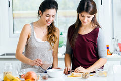 Two beautiful young women preparing cereal bowls in the kitchen. Stock Photography