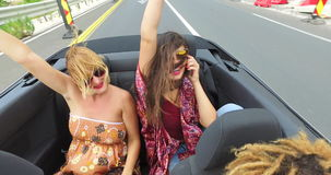 Two beautiful young women raising their arms up while riding in convertible stock video
