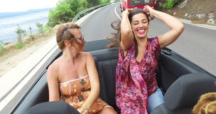 Two beautiful young women raising their arms up while riding in convertible stock video footage