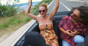 Two beautiful young women raising their arms up while riding in convertible. Two beautiful young women raising their arms up while partying in convertible stock footage
