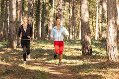 Two beautiful young women running through the park Stock Images