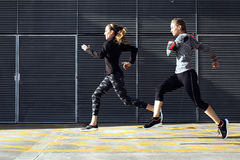 Two beautiful young women running in urban environment. Royalty Free Stock Photo