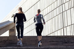 Two beautiful young women running in urban environment. Royalty Free Stock Image