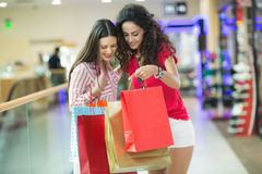 Two beautiful young women in a shopping center. Checking bags Stock Photography