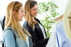 Two beautiful young women shopping in a clothes shop. Royalty Free Stock Photos