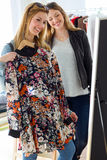 Two beautiful young women shopping in a clothes shop. Royalty Free Stock Images